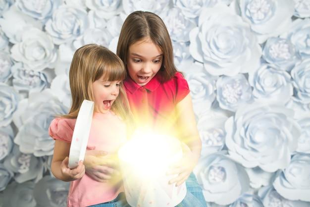 분홍색 블라우스를 입은 놀란 두 소녀가 근처에 앉아서 둥근 상자에 있는 선물을 엽니다. 배경에 흰색 꽃
