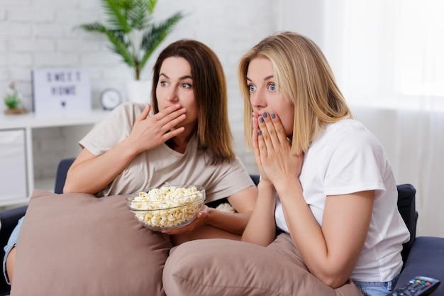 Две удивленные молодые женщины едят попкорн и смотрят что-то по телевизору