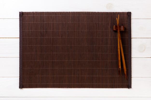 空の竹マットまたはコピースペースを持つ白い木製の背景平面図上の木製プレートと2本の寿司箸。空のアジア料理
