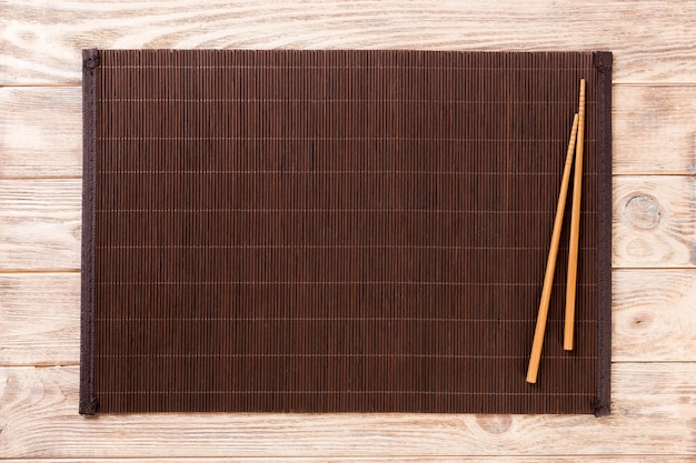 Two sushi chopsticks with empty bamboo mat or wood plate on brown wooden background top view with copy space. empty asian food background Premium Photo