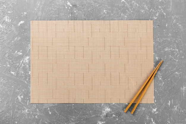 Two sushi chopsticks with empty bamboo mat or wood plate on cement wall top view with copy space. empty asian food wall