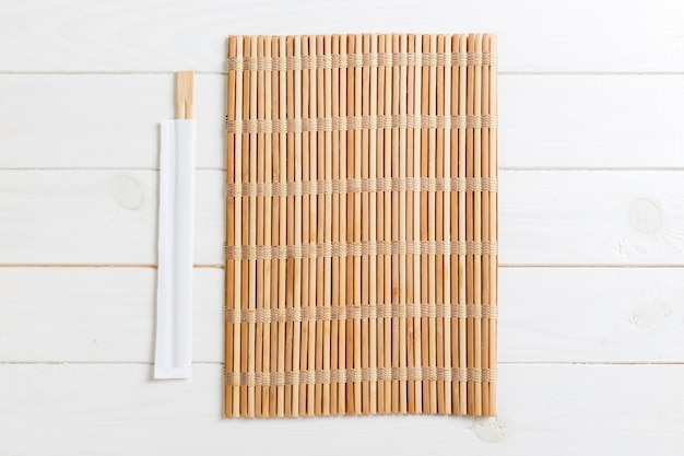 Two sushi chopsticks with empty bamboo mat or wood plate on wood