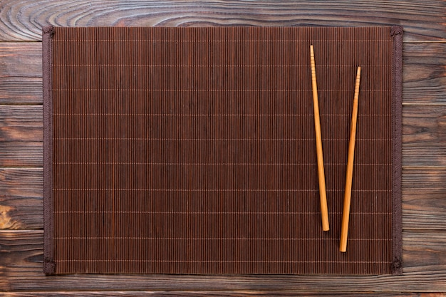 Two sushi chopsticks with empty bamboo mat or wood plate on wooden background