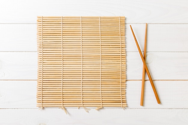 Two sushi chopsticks with empty bamboo mat on wood