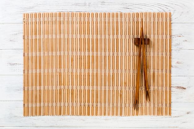 空の茶色の竹マットまたはコピースペースを持つ白い木製の背景平面図上の木製プレートと2本の寿司箸。空のアジア料理の背景