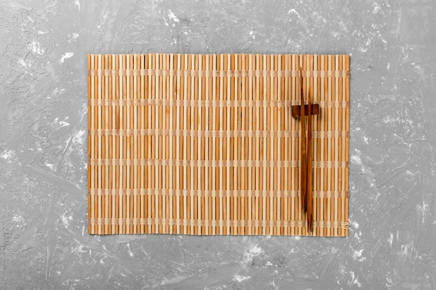 Two sushi chopsticks with empty brown bamboo mat or wood plate on cement background top view with copyspace. empty asian food background