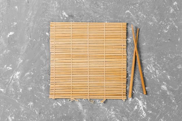 Two sushi chopsticks with empty brown bamboo mat or wood plate on cement background