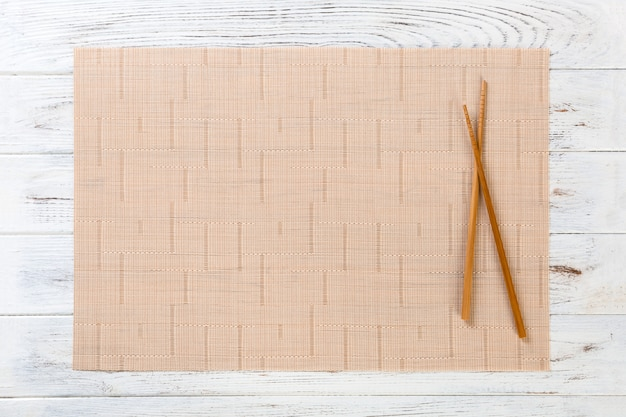 Two sushi chopsticks with empty brown bamboo mat or wood plate on white wooden background top view with copy space. empty asian food background