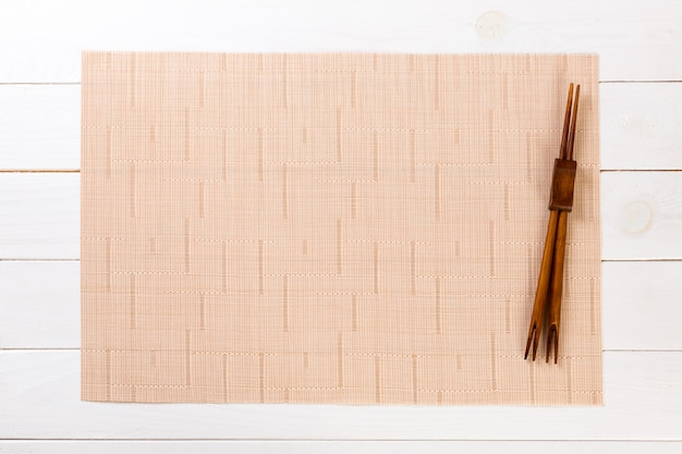 Two sushi chopsticks with empty brown bamboo mat or wood plate on white wooden  top view with copyspace. empty asian food background