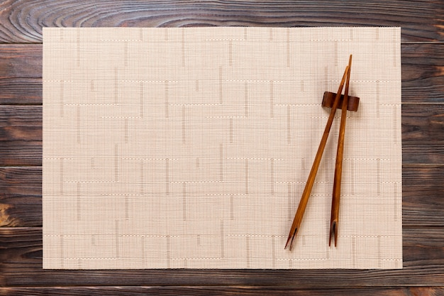 Two sushi chopsticks with empty brown bamboo mat or wood plate on wood