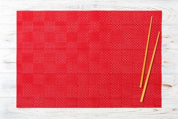 Две палочки для суши с пустой красной скатертью, салфетка на белой деревянной поверхности вид сверху с копией пространства