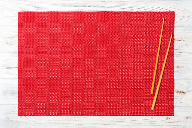 Two sushi chopsticks with empty red tablecloth, napkin on white wooden surface top view with copy space