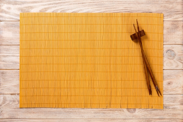 Two sushi chopsticks with empty yellow bamboo mat  wood plate on brown wooden background top view with copy space. empty asian food background
