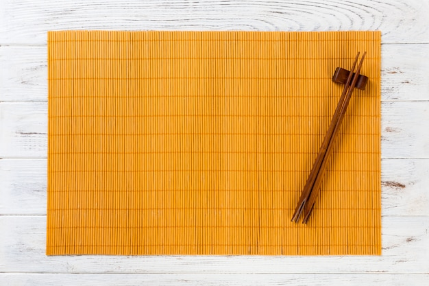 Two sushi chopsticks with empty yellow bamboo mat or wood plate on white wooden background top view with copyspace. empty asian food background