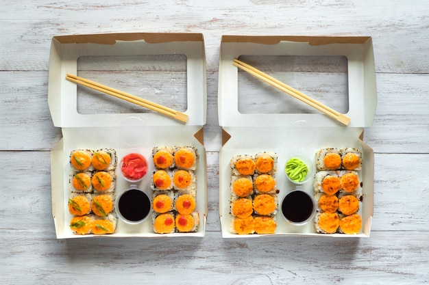 Two sushi set in a box on a wooden table. street food