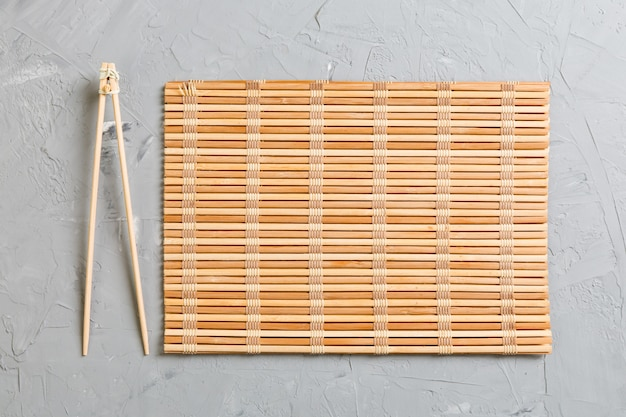 Two sushi training sticks with empty bamboo mat or wood plate on stone
