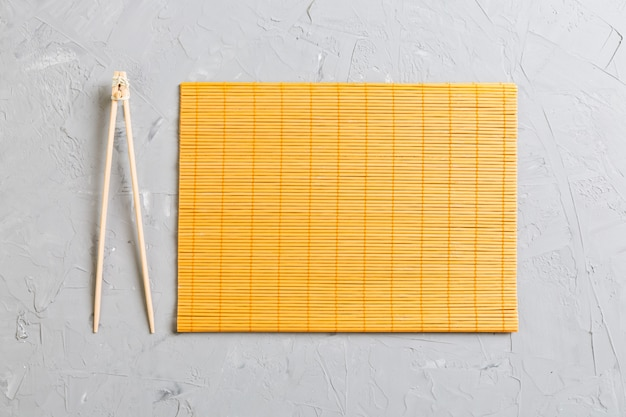Two sushi training sticks with empty bamboo mat