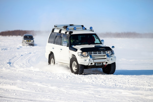 Two suvs moving at snow field in winter