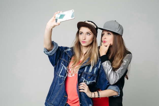 Two swag sisters taking self portrait on call phone.