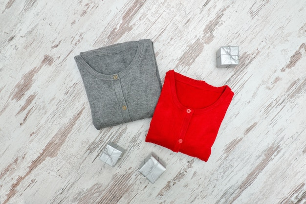 Two sweaters and silver boxes on a wooden background