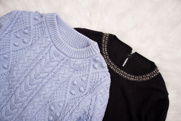 Two sweaters on white fur. fashionable , top view
