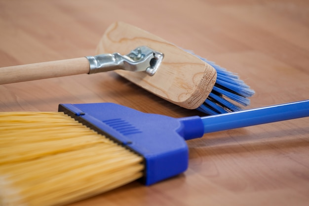 Two sweeping brooms on wooden floor