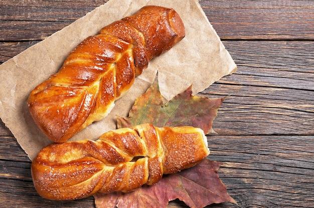 古い木製のテーブルに2つの甘い編みパン