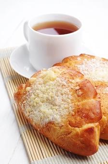 흰 탁자에 있는 두 개의 달콤한 만두와 차 한 잔