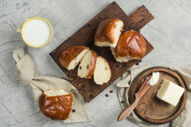 건포도와 함께 달콤한 빵 두 개를 버터와 우유 한잔으로 나무 판에 조각으로 자릅니다.