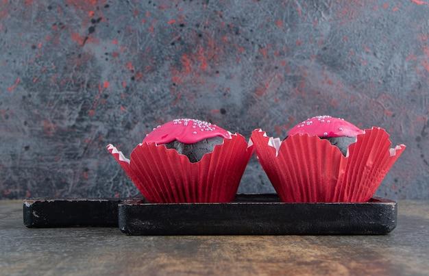ピンクのフロスティングと振りかける2つの甘いチョコレートドーナツ