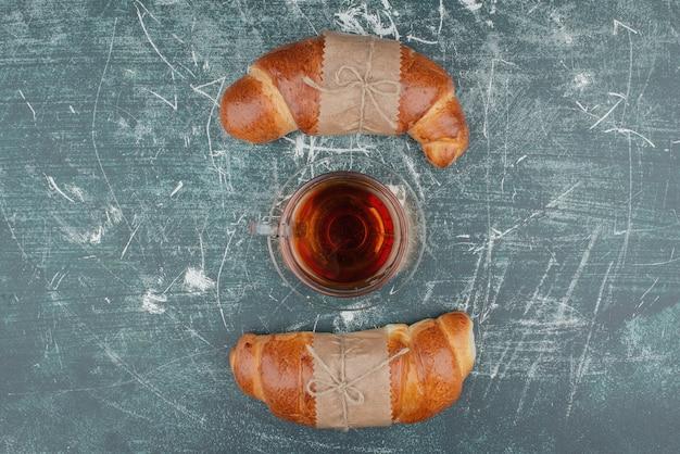 Due croissant dolci con tè caldo su marmo.