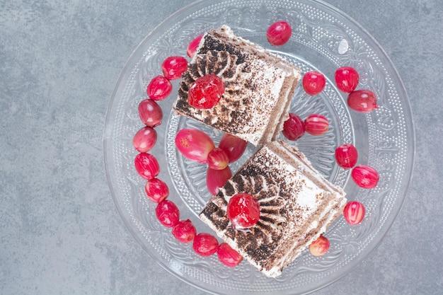 ガラス板にローズヒップが付いた2つの甘いおいしいケーキ