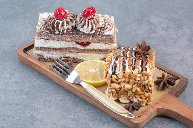木の板にスターアニスを添えた2つの甘くておいしいケーキ。