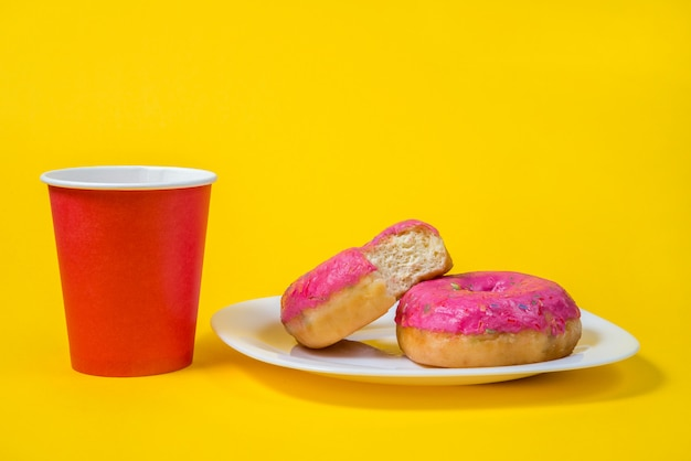 Two sweet half-eaten pink doughnuts on a white plate isolated on a yellow background