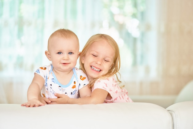 Two sweet happy caucasian children siblings girl and boy hide behind the white sofa in the room at home, portrait
