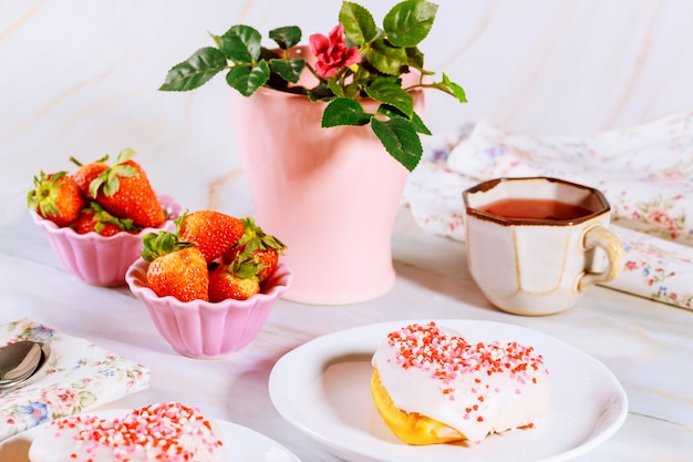 Two sweet heart shaped donut with white glaze and sprinkles on party table with tea, strawberries and rose.