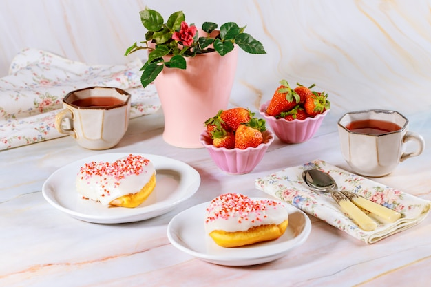 Two sweet and pink heart shaped donut with white glaze and sprinkles on party table with tea, strawberries and rose.