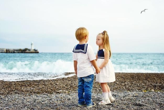 海の近くを歩いている2人の甘い幼児