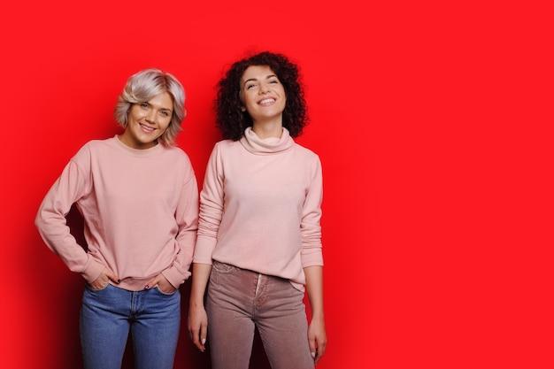같은 스웨터에 빨간색 포즈 두 달콤한 여자