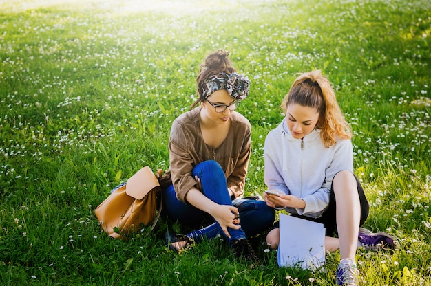 Two sylish girls sitting on the grass and using phone