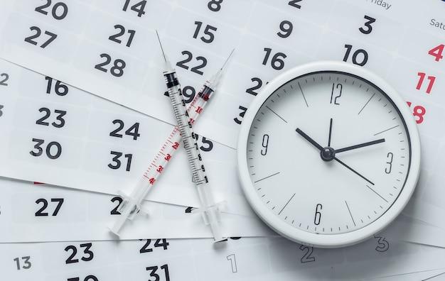 Два шприца и часы на крупном плане ежемесячного календаря. вакцинация
