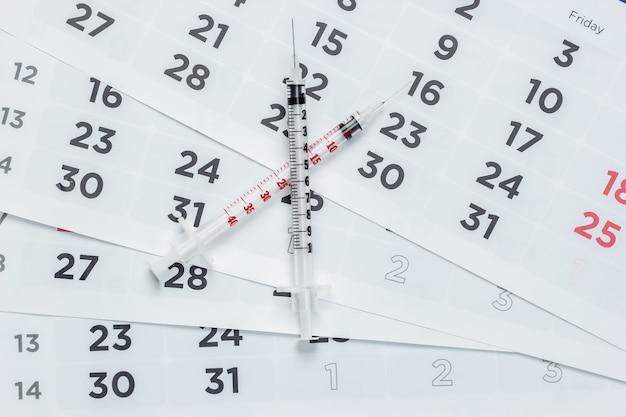 Два шприца на крупном плане ежемесячного календаря. вакцинация