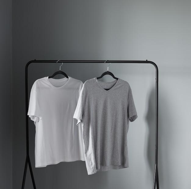 灰色の壁に黒いハンガーの中間色の2つのtシャツ