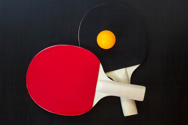 Two table tennis or ping pong rackets and ball on a black table