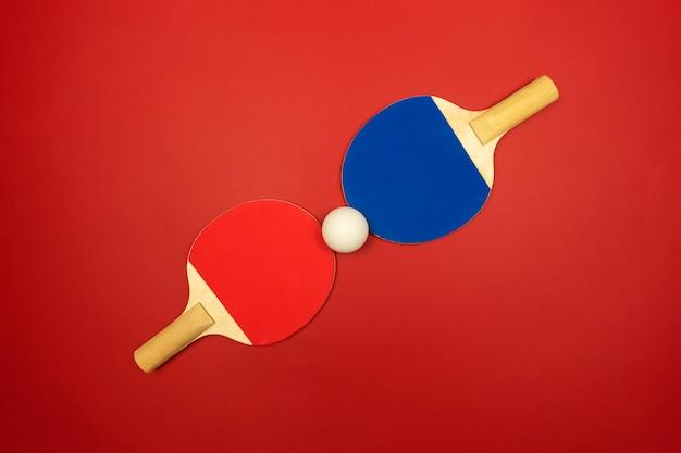 Две ракетки для настольного тенниса лежат напротив друг друга и готовы к соревнованиям по настольному теннису.