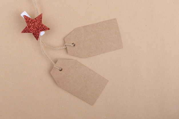Two tags of recycled kraft paper hanging from a rope decorated with a clothespin with a red christmas star