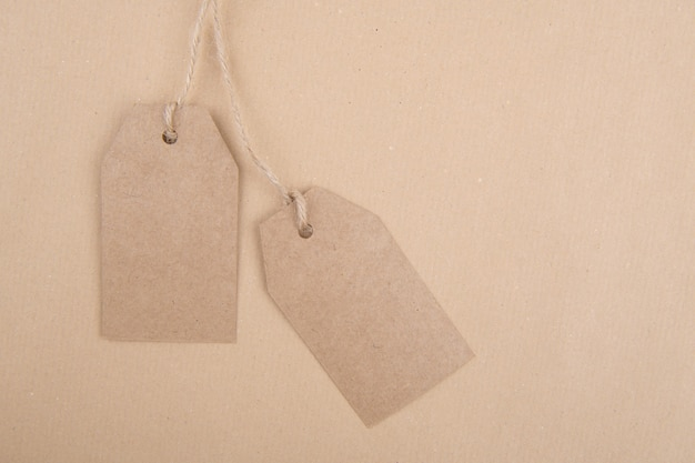 Two tags of recycled kraft paper  hanging from a rope on kraft paper. flat lay