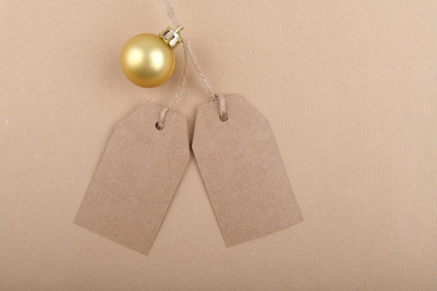 Two tags of recycled kraft paper for packaging hanging from a rope decorated with a golden christmas ball