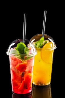 Two take away glasses with strawberry and orange lemonade isolated on black