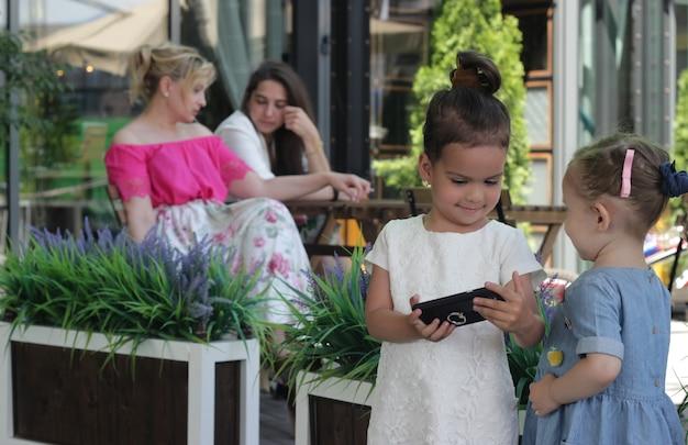 Две говорящие женщины и две девушки со смартфоном. беседа